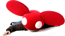 Image of DeadMau5 with red DeadMau5 mask lying on the ground.